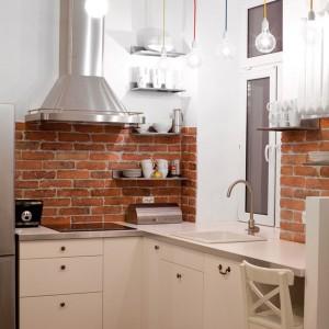 W przestrzeni kuchni zestawiono ze sobą elementy typowo loftowe, jak industrialne oświetlenie i imitacja cegły nad blatem z delikatnymi, kobiecymi meblami kuchennymi. Projekt: Magdalena Ilmer, Boho Studio. Fot. Boho Studio.