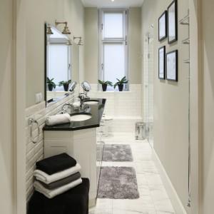 Chociaż łazienka jest wąska i z pozoru nieustawna, to biały kolor, połyskujące materiały i lustra optycznie ją powiększyły, a funkcjonalny układ sprawił, że wygodnie korzystają z niej dwie osoby. Projekt: Iwona  Kurkowska. Fot. Bartosz Jarosz.