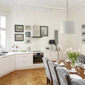Biała, piękna kuchnia w stylu klasycznym. Połyskujące fronty mebli nadają wnętrzu wrażenie lekkości i czystości. Sztukaterie na białym suficie wprowadzają do wnętrza element elegancji. Z bielą idealnie harmonizuje delikatna szarość tekstylnych abażurów lamp i tapicerowanych siedzeń krzeseł. Całość ociepla naturalny parkiet drewniany i stylizowany, solidny stół z drewna. Projekt: Iwona Kurkowska. Fot. Bartosz Jarosz.