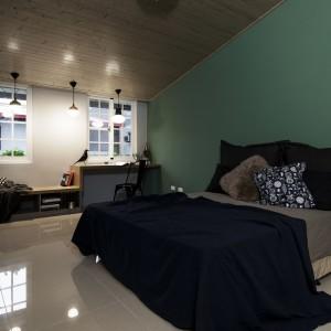 Duża sypialnia na trzecim piętrze to prawdziwe królestwo Pana i Pani domu. Obszerne łóżko, mnóstwo przestrzeni, piękne tekstylia i połyskująca posadzka prezentują się nad wyraz elegancko. Ścianę za łóżkiem pokrywa ciemnozielona pastelowa farba, a sufit wyłożono, budującymi przytulność we wnętrzu, drewnianymi deskami. Projekt: HAO Design Studio. Fot. Joey Liu.