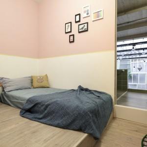 Sypialnia na drugim piętrze, połączona została z łazienką, z której rozpościera się widok na taras z ogrodem. We wnętrzu dominują delikatne pastelowe kolory, w palecie brązów, beżów i bladego różu. Projekt: HAO Design Studio. Fot. Joey Liu.