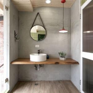 Beże i szarości - tak prezentuje się strefa umywalki w jednej z łazienek na drugiej kondygnacji. Surowość ścian zamknięto w drewniane ramy - na suficie i podłodze. Niewielka nablatowa umywalka, vintage'owe lustro i loftowa umywalka dopełniają całości, tworząc oszczędną, ale efektowną aranżację. Projekt: HAO Design Studio. Fot. Joey Liu.