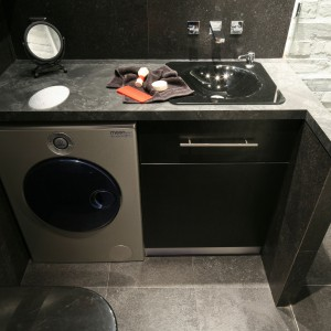 W małej łazience można zmieścić wszystkie niezbędne sprzęty, np. kosztem szafki podumywalkowej  zmniejszonej o połowę. Znalazło się tu miejsce także na pralkę, która znajduje się pod blatem. Projekt: Dominik Respondek. Fot. Bartosz Jarosz.