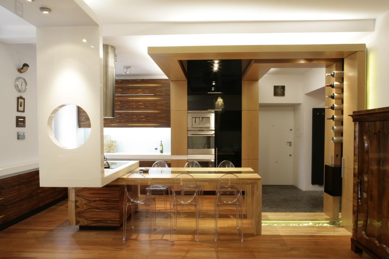W tym warszawskim mieszkaniu kuchnia odznacza się pięknymi wyraźnymi słojami drewna, które świetnie pasują do białych ścian i jaśniejszych drewnianych elementów. Projekt: Michał Swałtek. Fot. Bartosz Jarosz.