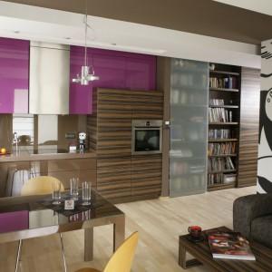 W tej kuchni tylko część zabudowy wykonano w ciemnym drewnianym kolorze. Stanowi on nawiązanie do zabudowy salonu, z którym kuchnia tworzy otwartą przestrzeń. Projekt: Paweł Ejsmont. Fot. Bartosz Jarosz.