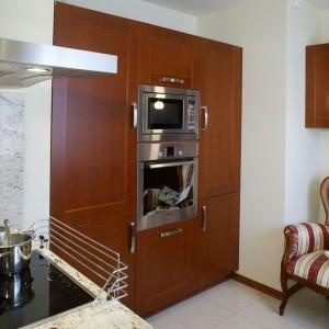 Zabudowa kuchenna w dość klasycznym stylu. Ciepły kolor drewna sprawia, że wnętrze jest bardzo przytulne. Projekt: Barbara Gryt. Fot. Monika Filipiuk-Obałek.
