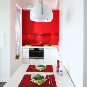Dzięki czerwonym szafkom niewielka kuchnia ma wyrazisty wygląd, przez co staje się bardziej widoczna na mapie mieszkania. Projekt: Iza Szewc. Fot. Bartosz Jarosz.