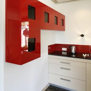 Czerwone, lakierowane szafki pełnią nie tylko funkcję praktyczną. Są także nie lada ozdobą białej ściany kuchni. Projekt: Jolanta Kwilman. Fot. Bartosz Jarosz.