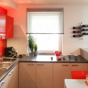 Ognista czerwień i jasny kolor drewna w ciepłym odcieniu to duet, który nada oryginalny wygląd każdej nowoczesnej kuchni. Wnętrze jest odważne ale stonowane, gdyż dominują w nim meble w jasnym kolorze. Projekt: Marta Kruk. Fot. Bartosz Jarosz.