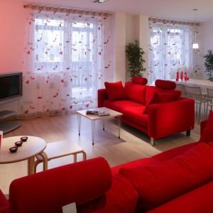 To wnętrze zdecydowanie zdominowały czerwone meble wypoczynkowe i nawiązujące do nich wzorami firany. Projekt: Piotr Grzywacz. Fot. Tomasz Markowski.
