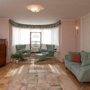 Stylizowany salon z wykuszowym oknem, w którym w oczy rzucają się przede wszystkim bogate zasłony i witryna prezentująca piękną zastawę. Projekt: Małgorzata Dzięgielewska. Fot. Paweł Supernak.
