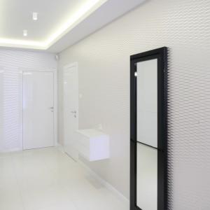 Długi przedpokój skąpano w bieli, która optycznie go powiększa. Efekt ten potęguje lśniąca tapeta z delikatnym wzorem. Projekt: Lucyna Kołodziejska. Fot. Bartosz Jarosz.
