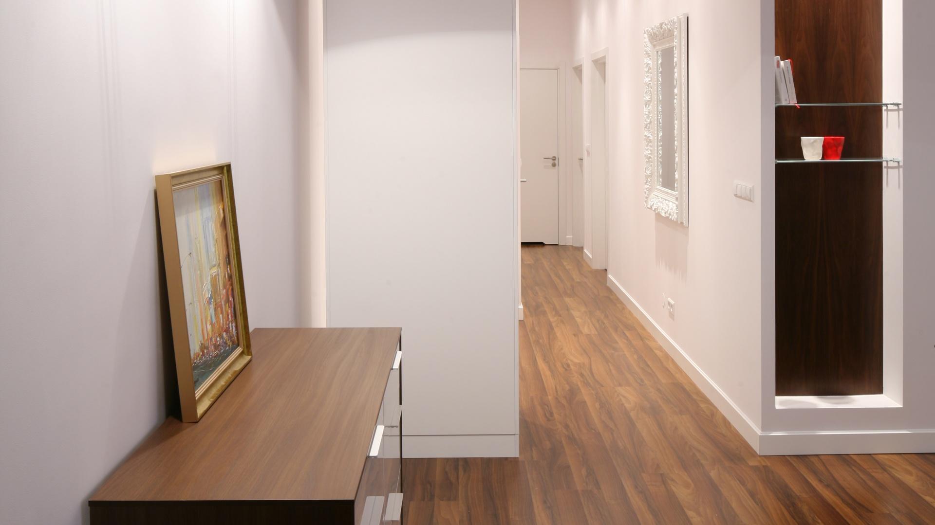 Wąski korytarz stanowi ciąg komunikacyjny pomiędzy poszczególnymi pomieszczeniami. Urządzony w czystej bieli, która optycznie powiększa przestrzeń, ocieplony został drewnianymi elementami. Projekt: Katarzyna Merta Korzniakowo. Fot. Bartosz Jarosz.