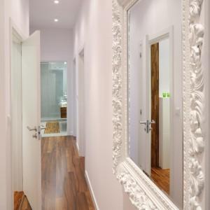 Wąską przestrzeń korytarza optycznie powiększa nie tylko biel, ale też lustro, którego rama dodatkowo stanowi elegancki element dekoracyjny. Projekt: Katarzyna Merta Korzniakowo. Fot. Bartosz Jarosz.
