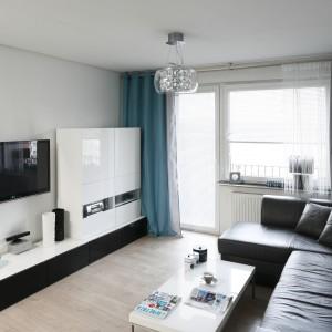 Wnętrze jest nowoczesne, ale i przytulne. Cała przestrzeń została spójnie zaprojektowana, zarówno pod względem zastosowanej kolorystyki, jak i materiałów wykończeniowych. Zimne w odbiorze biele i czernie ociepla drewno w jasnym wybarwieniu. Projekt: Marta i Tomasz Kilan. Fot. Bartosz Jarosz.