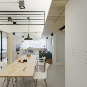 Centrum wnętrza stanowi otwarta przestrzeń, w obrębie której urządzono niewielki salon z telewizorem, jadalnię i aneks kuchenny. Projekt: KC Design Studio. Fot. KC Design Studio.