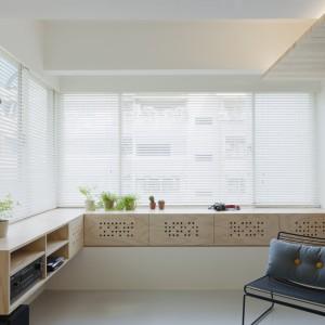 Narożne okna wpuszczają do wnętrza sporą ilość dziennego światła. Wzdłuż ściany, pod oknem, parapet zastąpiono zabudową, z ażurowymi wstawkami i praktycznymi półkami. Projekt: KC Design Studio. Fot. KC Design Studio.