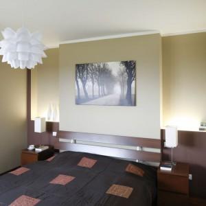 W sypialni zadbano o właściwy dobór oświetlenia. Na stolikach nocnych znajdziemy praktyczne lampki nocne, ogólne oświetlenie zapewnia wisząca lampa nocna o ciekawiej formie. Dodatkowo, zaprojektowano dekoracyjne oświetlenie umieszczone na ścianie za łóżkiem. Fot. Bartosz Jarosz.