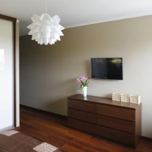 Naprzeciwko łóżka umieszczono komodę, która formą nawiązuje do pozostałych mebli w sypialni. Nad komodą umieszczono telewizor. Fot. Bartosz Jarosz.