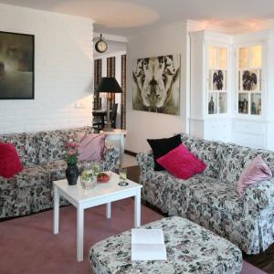 Urządzony w stylu skandynawskim salon urzeka elegancją podporządkowaną zasadzie aranżacyjnej prostoty. Wszechobecną biel ocieplają różowe poduchy, które doskonale współgrają z wzorzystymi kanapami. Projekt: Magdalena Kwiatkowska. Fot. Bartosz Jarosz.