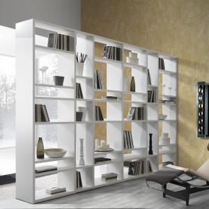 Zamiast tworzyć sztuczne podziały, możemy rozgraniczyć przestrzeń salonową od sypialnej praktycznym regałem. Stworzy on subtelną granicę oraz uporządkuje książki czy bibeloty. Fot. Giessegi.