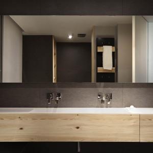 Ściany w łazience pokrywa wyrazista czerń, która pięknie kontrastuje z jasnym drewnianym dekorem. Całość zamknięto w kubistyczne formy. Projekt: Coblonal Arquitectura. Fot. Sara Riera.