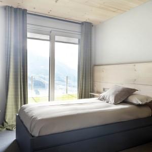 W sypialniach królują stonowane, subtelne barwy. Szarość pięknie komponuje się z jasnym drewnem. Projekt: Coblonal Arquitectura. Fot. Sara Riera.