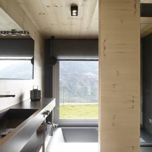 Płytka umywalka o geometrycznej formie chowa się estetycznie w blacie, wykonanym z tego samego materiału. Ciemna kolorystyka jest kontynuowana na ścianach, a przełamuje ją ciepły kolor drewna. W bezpośrednim sąsiedztwie okna usytuowano, chowającą się w podłodze, wannę. Projekt: Coblonal Arquitectura. Fot. Sara Riera.