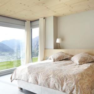Sypialnię rozświetlają panoramiczne przeszklenia, z widokiem na malowniczy krajobraz, oraz jasne barwy materiałów wykończeniowych. Projekt: Coblonal Arquitectura. Fot. Sara Riera.
