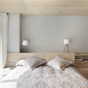 Funkcję zagłówka łóżka pełni zabudowa, zastępująca jednocześnie szafki nocne. Przechodzi ona w otwarte półki, a następnie w wysoką pod sam sufit szafę, mogącą posłużyć za garderobę. Projekt: Coblonal Arquitectura. Fot. Sara Riera.