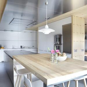 Kuchnię tworzy zabudowa jednorzędowa pod ścianą, wysoka zabudowa, pełniąca rolę ścianki działowej pomiędzy kuchnią i jadalnią, oraz obszerna wyspa kuchenna z powierzchnią do gotowania, przechodząca w blat stołowy. Projekt: Coblonal Arquitectura. Fot. Sara Riera.