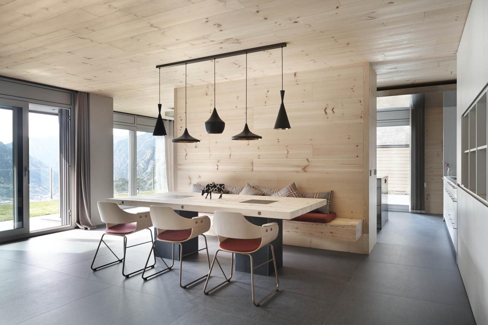 Element działowy pomiędzy kuchnią a jadalnią, od strony tej drugiej pełni rolę siedziska przy stole. Projekt: Coblonal Arquitectura. Fot. Sara Riera.
