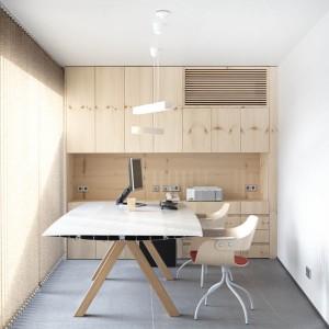 Zabudowa meblowa pod sam sufit pozwala zaoszczędzić przestrzeń w pomieszczeniach. W wąskim gabinecie pozwoliła usytuować sporych rozmiarów biurko i towarzyszące mu dwa krzesła. Projekt: Coblonal Arquitectura. Fot. Sara Riera.