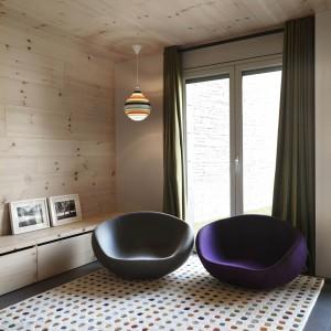 Fantazyjne oświetlenie, oryginalne meble wypoczynkowe i oryginalny, wzorzysty dywan budują we wnętrzu klimat pop art. Projekt: Coblonal Arquitectura. Fot. Sara Riera.