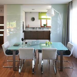 Częściowo otwartą kuchnię można zamknąć, przesuwając szklane drzwiczki. Ich powierzchnia pięknie komponuje się ze stołem, stojącym pomiędzy kuchnią a salonem. On sam stanowi dodatkowy element oddzielający funkcje strefy dziennej. Projekt: Magdalena i Marcin Konopka. Fot. Bartosz Jarosz.