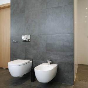 Grafitowe płytki z rysunkiem przetartego betonu zastosowane na ścianach i podłodze zapewniają surowy klimat - tak charakterystyczny dla wnętrz w stylu loft.  Projekt: Beata Kruszyńska. Fot. Bartosz Jarosz.