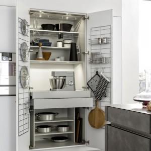 Niezwykle praktycznym i poręcznym pomysłem są dodatkowe uchwyty umieszczone na wewnętrznych drzwiach szafek, na których można trzymać pokrywki i lub przyprawniki, deski czy rękawice kuchenne. Fot. Leicht.