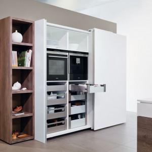 Najnowszym trendem jest tworzenie zabudowy kuchennej ukrytej za drzwiami przesuwnymi. Firma Hettich oferuje system okuć do drzwi przesuwnych InLine XL, które po zamknięciu tworzą jedną płaszczyznę. Nikt nie domyśli się nawet, że za drzwiami kryją się wygodne szuflady wewnętrzne mieszczące talerze czy produkty żywnościowe. Za frontami można ukryć także wbudowany sprzęt AGD. Fot. Hettich.
