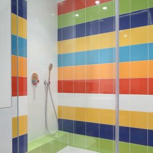 Zarówno ściany wnęki prysznicowej,  jak i podłogę pokrywają kwadratowe kafle ułożone w kolorowe poziome pasy. Projekt: Katarzyna Kiełek, Agnieszka Komorowska- Różycka. Fot. Bartosz Jarosz.