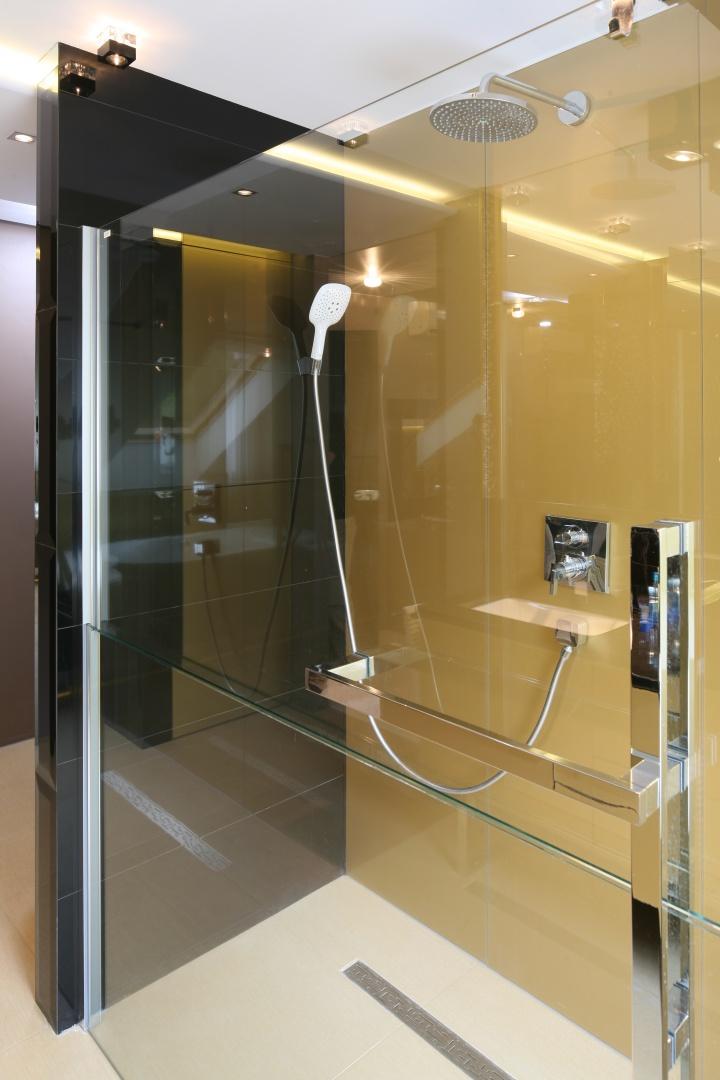 Ściana za prysznicem została zabezpieczona szkłem lakierowanym od spodu na złoty kolor, który świetnie współgra z innymi materiałami i kolorami składającymi się na aranżację tego luksusowego wnętrza. Projekt: Chantal Springer. Fot. Bartosz Jarosz.