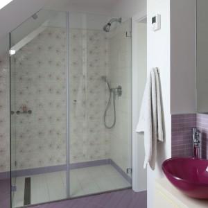 W łazience dla kilkuletniej dziewczynki króluje róż w odcieniu lila. Taki kolor maja m.in.  płytki podłogowe oraz kwiatki, które tworzą wzór na płytkach zastosowanych za ścianie w strefie prysznica. Projekt: Katarzyna Merta-Korzniakow. Fot. Bartosz Jarosz.