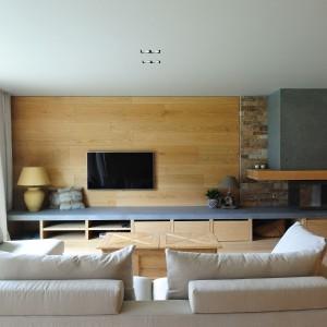 Telewizor i kominek zostały zlokalizowane na jednej ścianie, jednak w odległości wystarczająco dużej, aby płomienie nie zakłócały widoczności obrazów na ekranie. Strefę TV i kominka wyznaczają inne materiały: za telewizorem zastosowano drewno, za kominkiem - kamień. Projekt: Coblonal Arquitectura. Fot. Coblonal Arquitectura.