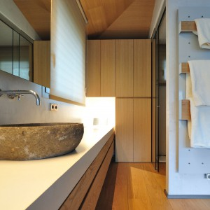 Efektownym i niezwykle oryginalnym akcentem w łazience jest nablatowa, kamienna umywalka. Grzejnik płytowy na ścianie pełni nie tylko funkcję grzewczą, ale i zastępuje wieszak. Projekt: Coblonal Arquitectura. Fot. Coblonal Arquitectura.