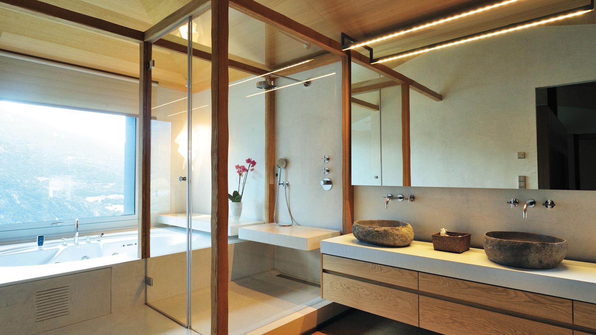Łazienka wygląda niczym ekskluzywny salon SPA. Kabinę prysznicową zaznaczają drewniane belki, pomiędzy które wpasowano przeszklenia. Przy oknie usytuowano wannę. Duże lustro optycznie powiększa przestrzeń. Projekt: Coblonal Arquitectura. Fot. Coblonal Arquitectura.