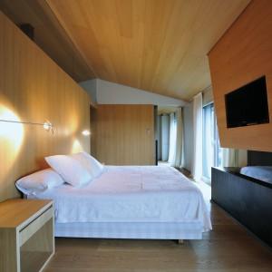 Unikalna sypialnia master zachwyca ilością użytego w niej drewna. Materiał znajduje się na suficie, zabudowie nad kominkiem oraz na ściance, przy której stanęło podwójne łóżko. Projekt: Coblonal Arquitectura. Fot. Coblonal Arquitectura.