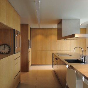 Niemal w całości drewnianą kuchnię urozmaica wyspa, w której fronty i blat wykonano ze stali inox. Projekt: Coblonal Arquitectura. Fot. Coblonal Arquitectura.