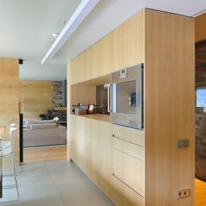 Przestrzeń kuchni zamyka wysoka zabudowa, w której zainstalowano sprzęt AGD. Projekt: Coblonal Arquitectura. Fot. Coblonal Arquitectura.