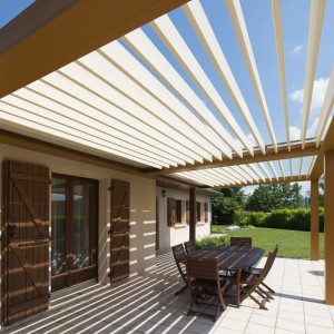 Aluminiowa pergola umieszczona została na całej długości tarasu. Kolorystyka nawiązuje do elewacji budynku. Fot. Installux Aluminium.