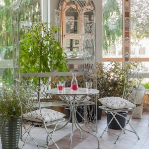Metalowa, bogato dekorowana, biała ławeczka z pergolą wprowadzi do każdego ogrodu magiczny nastrój. Fot. SODO.