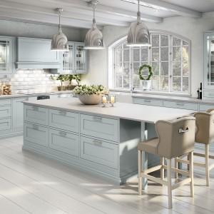 Wyspa kuchenna nie jest domeną jedynie nowoczesnych kuchni. Tutaj szeroki model pięknie prezentuje się zamknięty w klasyczną formę, z frezowanymi drzwiczkami w delikatnym, błękitnym kolorze. Fot. Sigdal, kuchnia Scala.